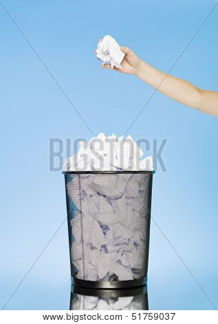 Human trowing a paper to a wastebasket on blue background