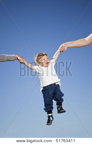 Child hanging in the air between parents hands