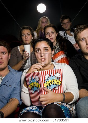 Afraid young woman at the movie theater with bag of popcorn