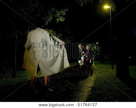 Two women laughing at a Flasher at night in the park