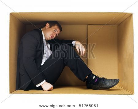 Businessman in a tight cardboard box isolated on white background