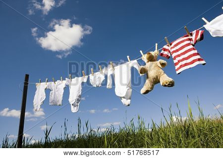 Baby Clothing and a teddybear on a clothesline towards blue sky
