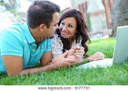 Attractive Couple On Grass With Computer