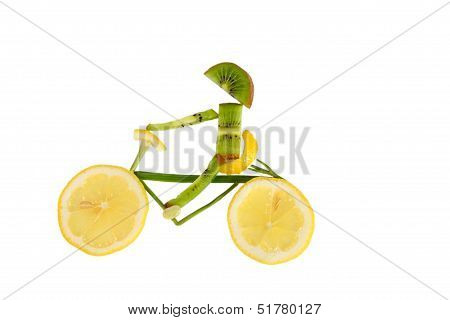 Healthy Eating. Funny Little Man Of The Kiwi Slices Rides A Bicycle Made out Of A Lemon.