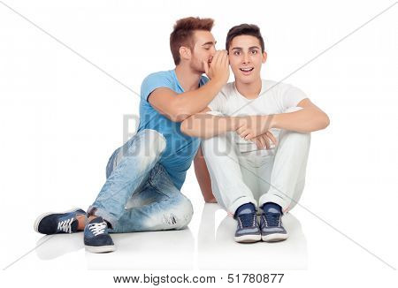 Two brothers whispering isolated on a white background