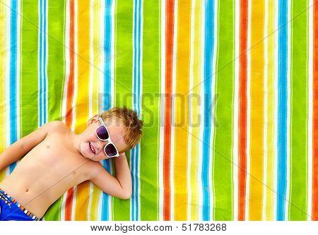 Happy Kid Sunbathing On Colorful Blanket