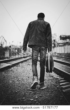 Young Man With Guitar Case In Hand Is Going Away. Rear View, Black And White