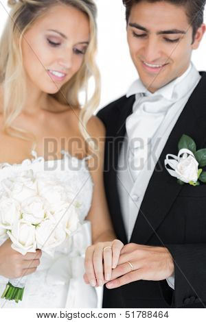 Smiling young married couple wearing wedding rings looking at them