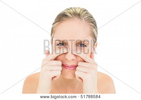 Frowning fresh blonde woman pressing her nose on white background