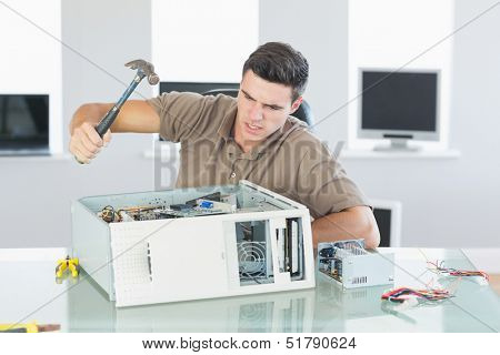 Attractive angry computer engineer destroying computer with hammer in bright office
