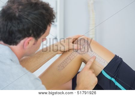 Physiotherapist checking knee with goniometer in bright office