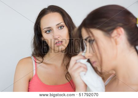 Crying woman sitting in the living room with her concerned friend