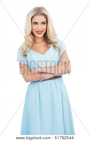 Smiling blonde model in blue dress posing crossed arms on white background