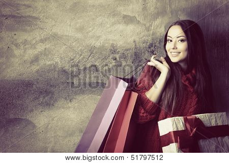 beautiful young woman holding colored shopping bags and gift box over grunge concrete wall, holiday seasonal concept, toned