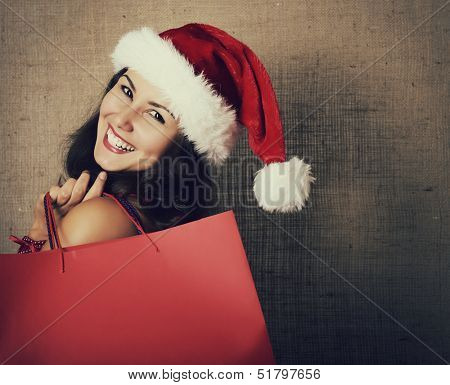 cheerful christmas woman in santa's hat smiling and holding shopping bags over canvas background