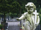 foto of abort  - Stone statue of a child holding a cross - JPG