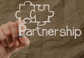 stock photo of partnership  - Hand drawing Partnership Puzzle with crumpled recycle paper background as concept - JPG
