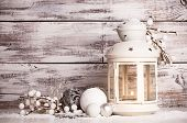 picture of twinkle  - Cristmas lantern with decorations and snow over white shabby wooden background - JPG
