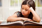 picture of storybook  - Portrait of a pretty little girl reading a storybook at home - JPG