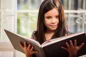 picture of storybook  - Little Hispanic girl relaxing and reading a storybook at home - JPG