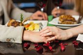 stock photo of rose close up  - Close up on loving couple holding hands during romantic dinner - JPG