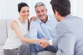 pic of beside  - Woman shaking hands with salesman sitting beside husband on couch at home - JPG