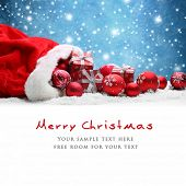 stock photo of joy  - Santa Claus red bag with Christmas balls and gift box on snow - JPG
