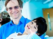 picture of biracial  - Handsome Caucasian father in forties holding biracial disabled son in arms - JPG