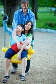 image of babysitting  - Big sister holding disabled brother on special needs swing at playground in park as father pushes - JPG