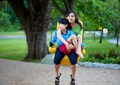 stock photo of babysitting  - Big sister holding disabled brother on special needs swing at playground in park - JPG