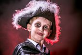 stock photo of warlock  - Little boy in halloween costume of pirate posing over dark background - JPG