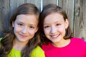 stock photo of little sister  - Happy twin sisters with different hairstyle smiling on wood backyard fence - JPG