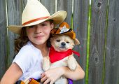 Beautiful cowboy kid girl holding chihuahua dog with sheriff hat in backyard wooden fence
