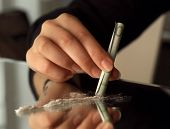 stock photo of drug dealer  - Human hand and drugs on a mirror - JPG