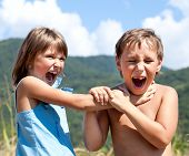 picture of strangled  - Angry boy and a girl scream and fight with each other outdoors - JPG