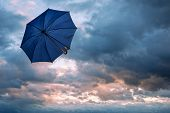 stock photo of rainy season  - umbrella and cloudy sky closeup - JPG