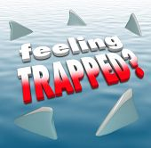 stock photo of fin  - Feeling Trapped words on an ocean surrounded by shark fins to illustrate hopelessness - JPG