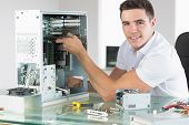 image of cpu  - Handsome cheerful computer engineer working at open computer in bright office - JPG