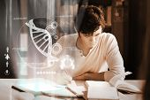 stock photo of dna  - Concentrated college student analyzing dna on digital interface in university library - JPG