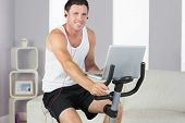 Sporty smiling man with earphones exercising on bike and holding laptop in bright living room