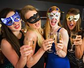 Attractive friends with masks on holding champagne glasses laughing at camera