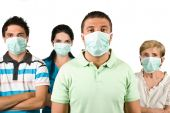 stock photo of swine flu  - Group of people with protective mask standing with hands crossed and looking at you isolated on white backgroundthis is a concept of protection from flu A - JPG