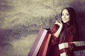 stock photo of single woman  - beautiful young woman holding colored shopping bags and gift box over grunge concrete wall - JPG