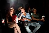 young people in a cinema attentively watching a movie, with popcorn and soda. An Asian woman feeding