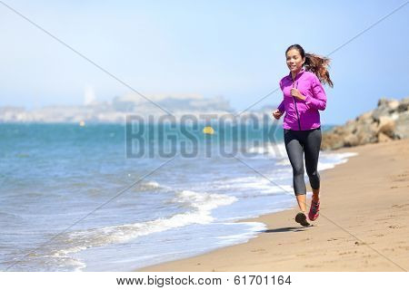 Woman running on San Francisco beach with Alcatraz in background. Smiling happy female athlete runner training on waterfront in San Francisco, California, USA. Mixed race fit fitness sport model.