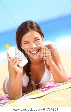 Suntan lotion woman applying sunscreen solar cream laughing having fun. Beautiful happy cute woman asian applying suntan cream from a plastic container to her nose with ocean in background.