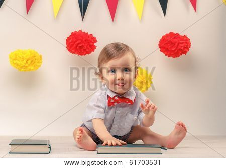 Pull faces cute baby boy looking straight ahead with little tongue out, sitting next to party flags