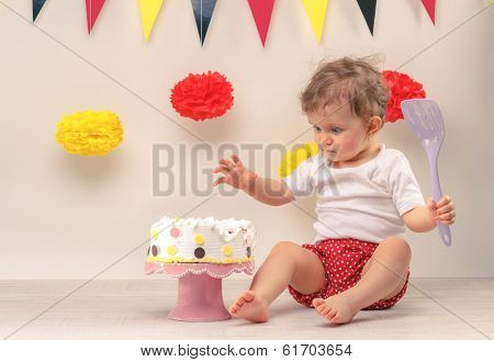 One year baby girl sitting next to a birthday cake and party flags