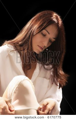 Woman Putting On White Stockings