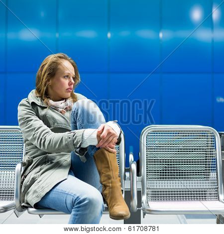 Sad and alone in a big city - Depressed young woman sitting in a metro station, feeling sorrow, regret